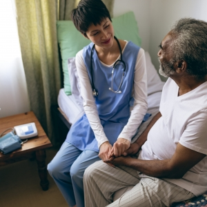High angle view of Asian female doctor and senior male patient interacting with each other at retirement home. They are holding hands.
